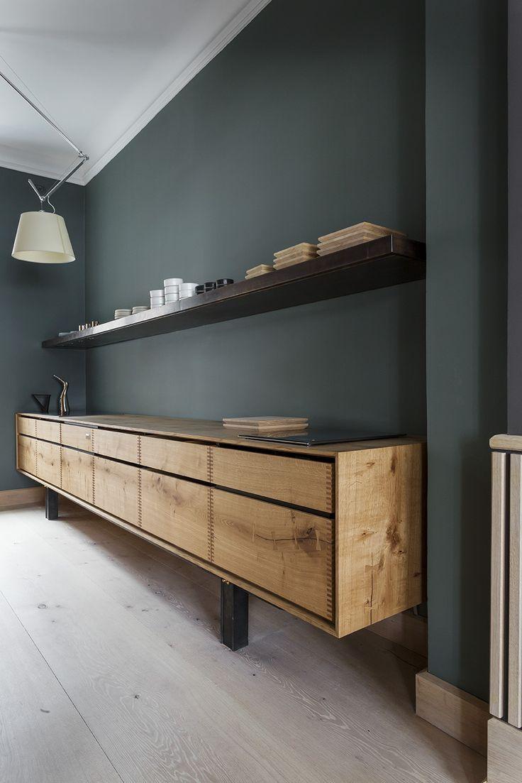 un mur vert profond et sourd rehaussé par un meuble bas tout en longueur en…