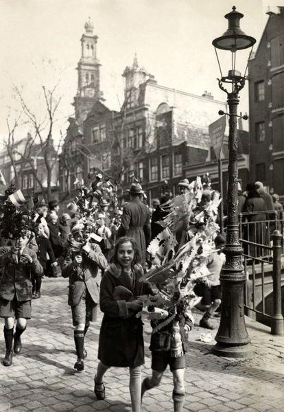 SFA003005382 Amsterdam (Nederland) Een palmpasenoptocht door de Jordaan. Kinderen lopen met hun versierde stokken. De Westertoren  steekt boven de huizen uit. 25 maart 1934.