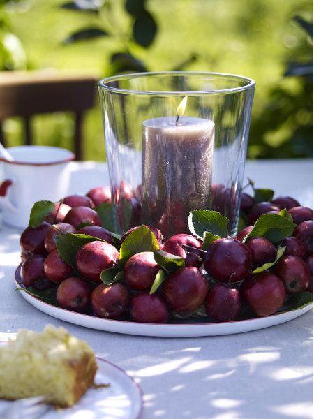 Kleine Zieräpfel wurden auf Steckmasse in Kranzform befestigt. Die Kerze schmückt zusätzlich die Kaffeetafel.
