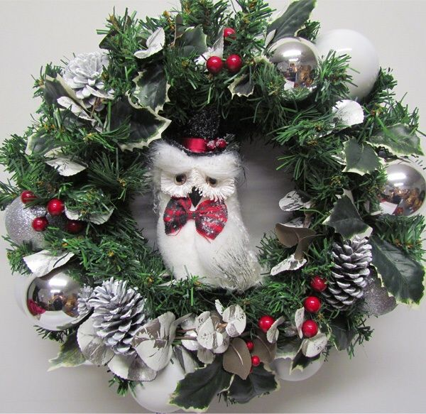 A winter wonderland wreath, with silver pinecones, holly berries and Christmas owl.