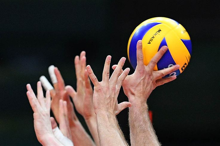 Polish players jump to block the ball during the men's qualifying volleyball match with Iran.