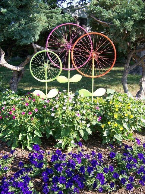 "Old bicycle rims painted bright colors make ""flowers"" in the garden"