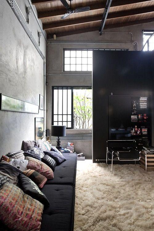 decoração sala de estar no estilo industrial com parede de concreto, tubulação aparente, sofá preto, cadeira design