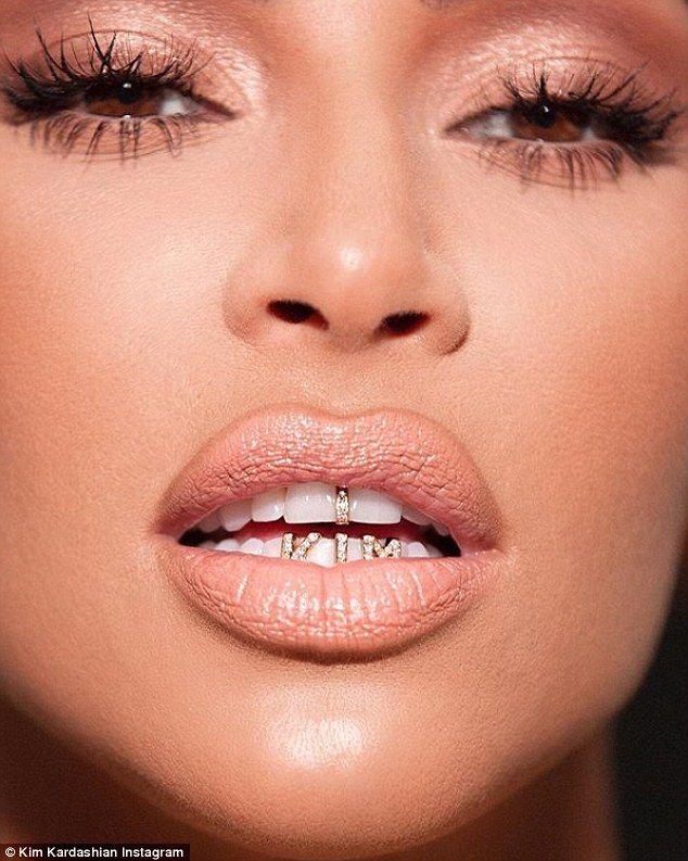 Kim Kardashian flaunts new name tag grills to promote KKW Beauty