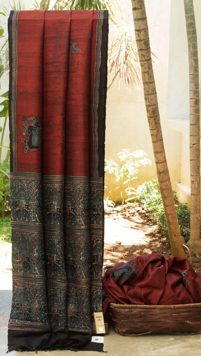 MAROON AJRAK DUPION SILK WITHELEPHANT PRINTS ON THE BODY AND PALLU. THE SIMPLE ASH BLUE, BLACK AND MAROON BORDER IS AN ADDED BEAUTY TO THE SAREE.