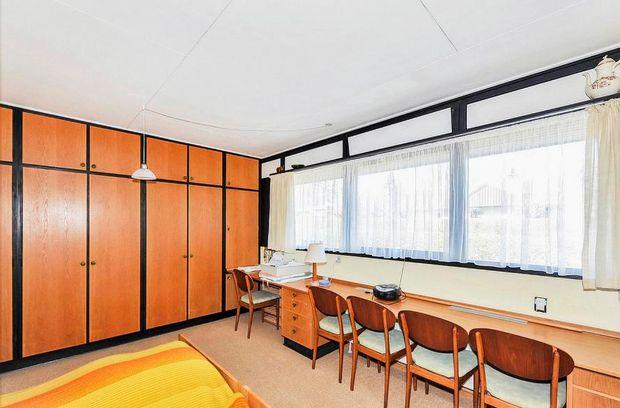 Soveværelset ligner i høj grad sig selv. Familien har bevaret de smukke, indbyggede skabe, og der er også kontorplads derinde. Til gengæld er gulvtæppet fjernet, og der er støbt et moderne betongulv.