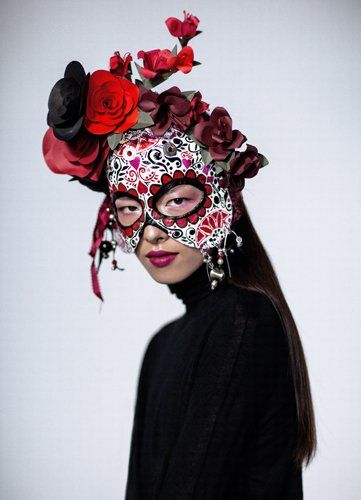 """The """"Day of the Dead"""" mask consists of a papier-mâché base paired with satin ribbon, acrylic paint, pastel drawing paper, beading, ribbon, paillettes, Indian coin paillettes, rhinestones, armature wire, floral tape, and hemp chording."""