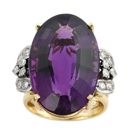 Large fancy cut amethyst dinner ring   mid 20th century   Oblong cut amethyst in yellow gold prong setting, framed on either side by petite round cut diamonds in platinum topped setting.