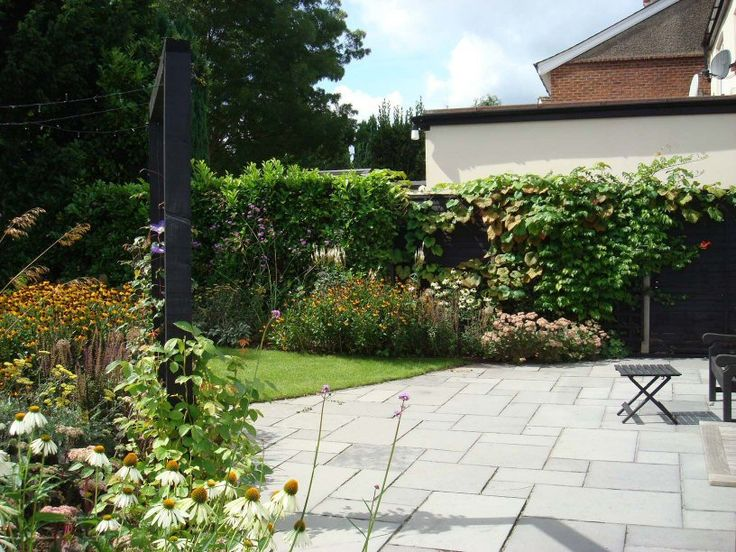Sunny terrace surrounded by perennial plants and climber in this long, narrow, garden design in Woking, Surrey. Designed by Linsey Evans Garden Design www.linseysgarden...