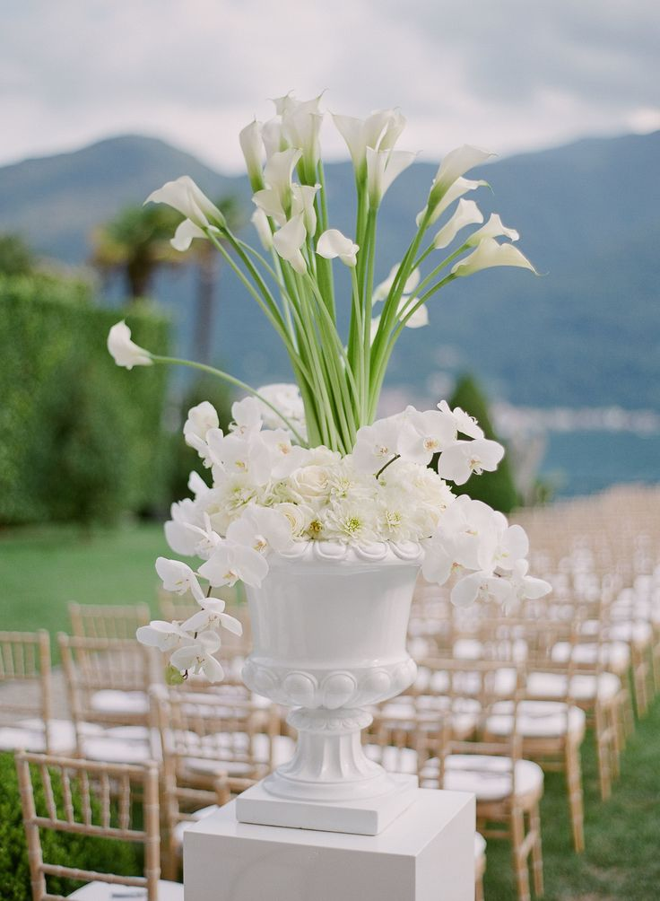 An all white modern urn for a lakeside ceremony. These urns framed the entrance to the aisle and the chuppah. by @TheLakeComoWeddingPlanner
