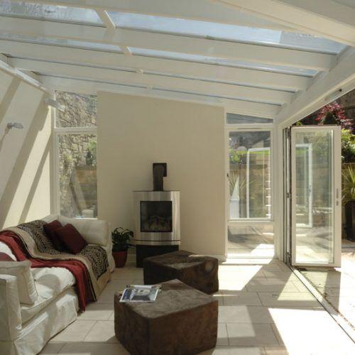 Garden room with bi-folding doors, white stone floor and wood-burning stove