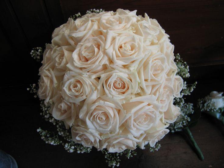 Kuppelformet brudebuket med Vendela rose og krans af brudeslør. Synlige stilke med hængende bånd fra bærestykket. (Rikke)