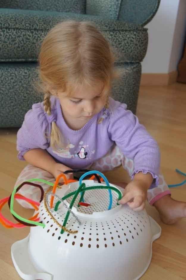 Auch mit bunten Pfeifenreinigern und einem Sieb kann man Kleinkinder beschäftigen.