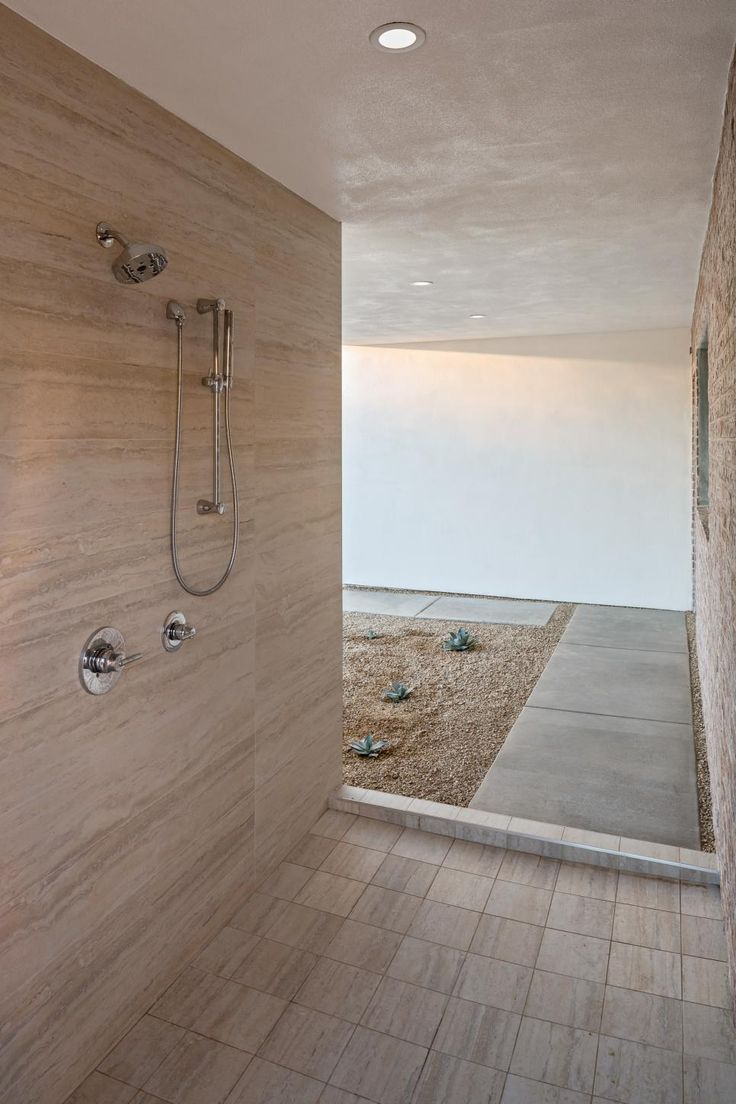 Recessed+lighting+illuminates+this+indoor-outdoor+shower+which+features+all-over+neutral+tile+and+chrome+shower+fixtures.+Neutral+gravel+covers+the+nearby+courtyard,+while+succulent+plants+provide+a+Southwestern+touch.