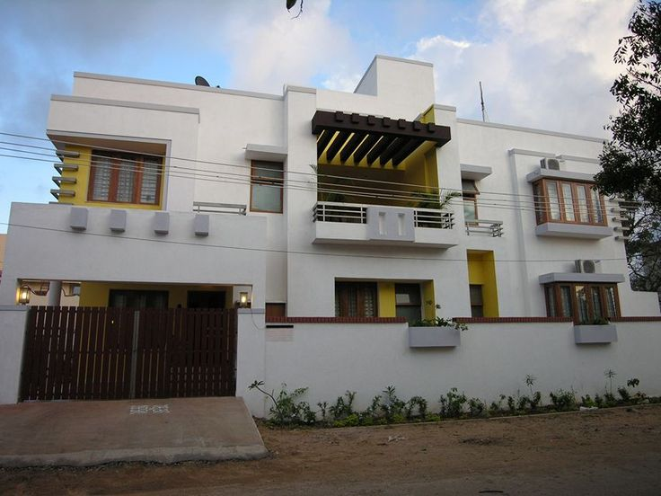 Exterior view of the house has multiple levels which has been painted in contrast yellow colour as highlights.