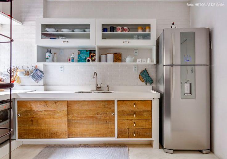 Cozinha branca com piso de cimento queimado e armário feito com madeira de demolição.