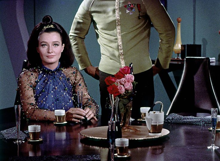 https://flic.kr/p/81BYra | Are Those Roses in Your Pocket or Are You Just Happy to See Me? | An entertaining frame of Diana Muldaur in the role of Dr. Miranda Jones in the TOS episode Is There In Truth No Beauty? Shatner has his opinion and blooms for the occasion, while Muldaur's expression is somewhat bemused. The rather ordinary prop tea cups and teapot are also easy to see in this shot as well as some detail in the costume worn by Muldaur. In the script Dr. Jones in fact could not see…