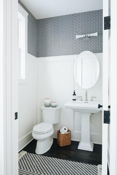 Transitional powder room with blue wallpaper above…