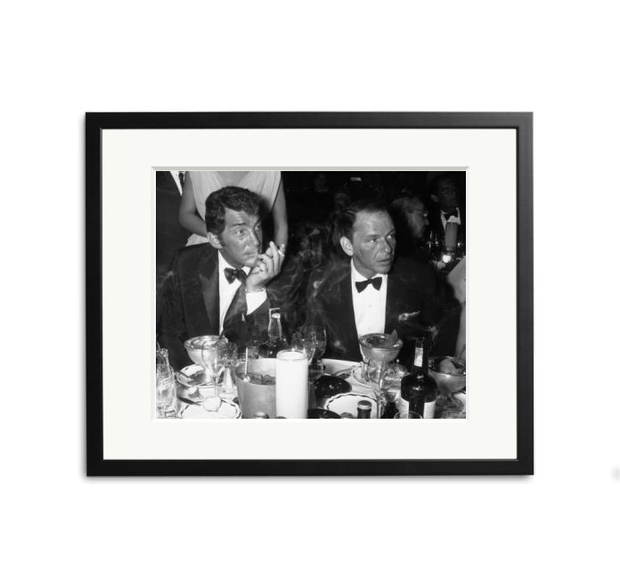 Dean Martin and Frank Sinatra attend the opening night performance of singer Eddie Fisher at the Coconut Grove, Hollywood, California.  Martin and Sinatra are sitting around a dinner table covered with drinks and appetizers
