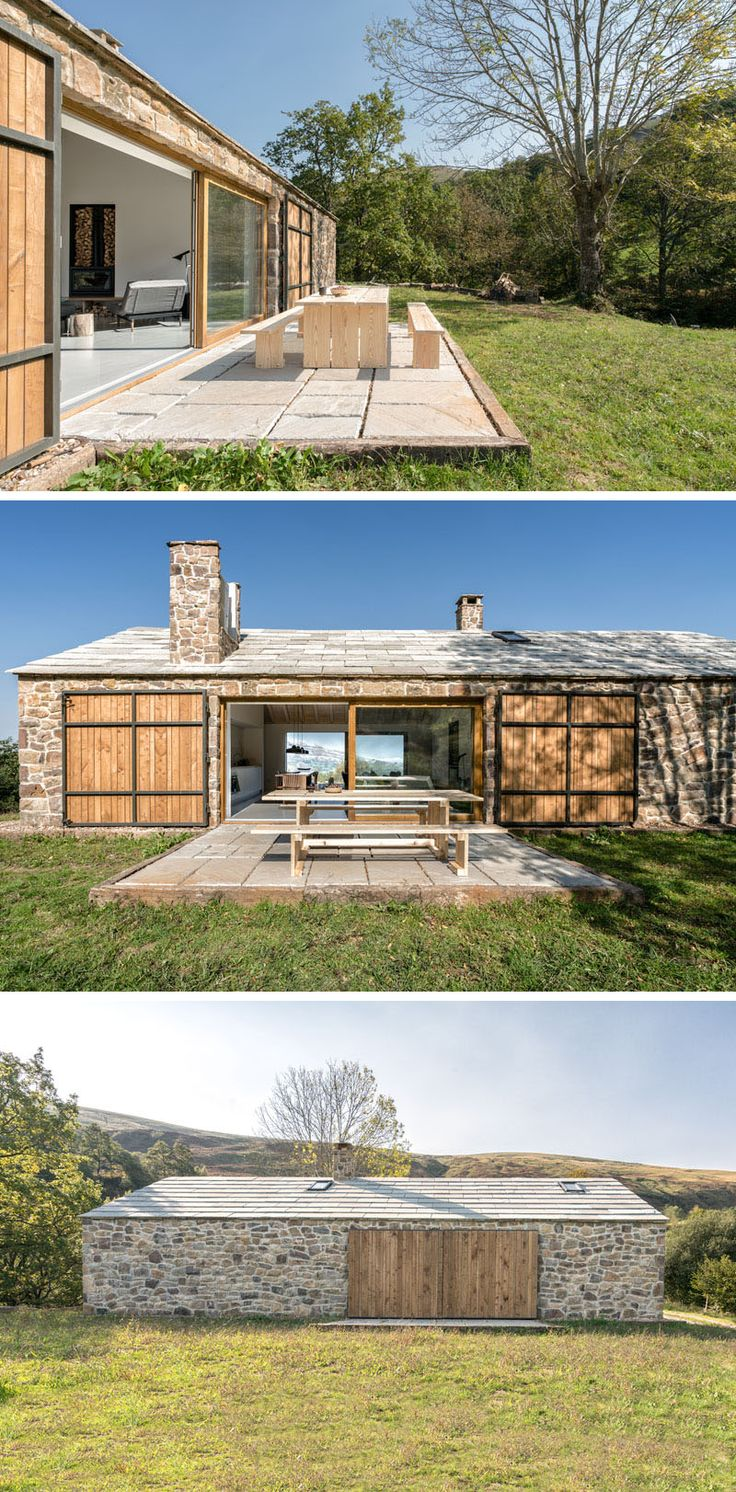 This contemporary stone cottage has an outdoor dining area that opens up a grassy field. Large wood and steel doors can be closed to protect the cottage from the elements, and provide privacy if needed. #StoneCottage #OutdoorDining #ContemporaryCottage