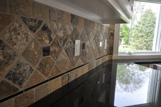 tile backsplash with dark countertops | black granite counter top with a stone tile backsplash design the tile ...