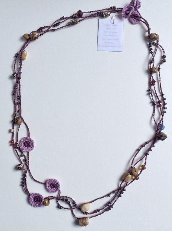 Ce collier délicat et élégant au crochet a été tout simplement effectué dans une dentelle unique chaîne intégrée avec le verre, céramique et perles en bois. Il a été laissé débloqué donc vous pouvez lutiliser comme sil vous plaît. Il permet jusquà trois ou quatre boucles autour de votre cou. Le modèle de couleur est un mélange de tons pourpres. Il a quelques motifs ronds comme décoration. Leffet est tout simplement magnifique.  Matériaux : Verre, perles en céramique et en bois ; 100 % fil…