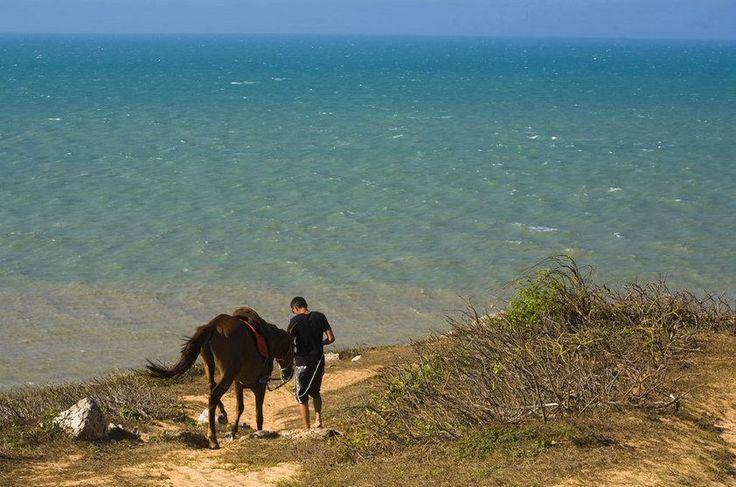 Turista no Morro do Serrote a caminho da Pedra Furada, região de formações rochosas de Jericoacoara