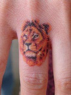 Tiny lion tattoo