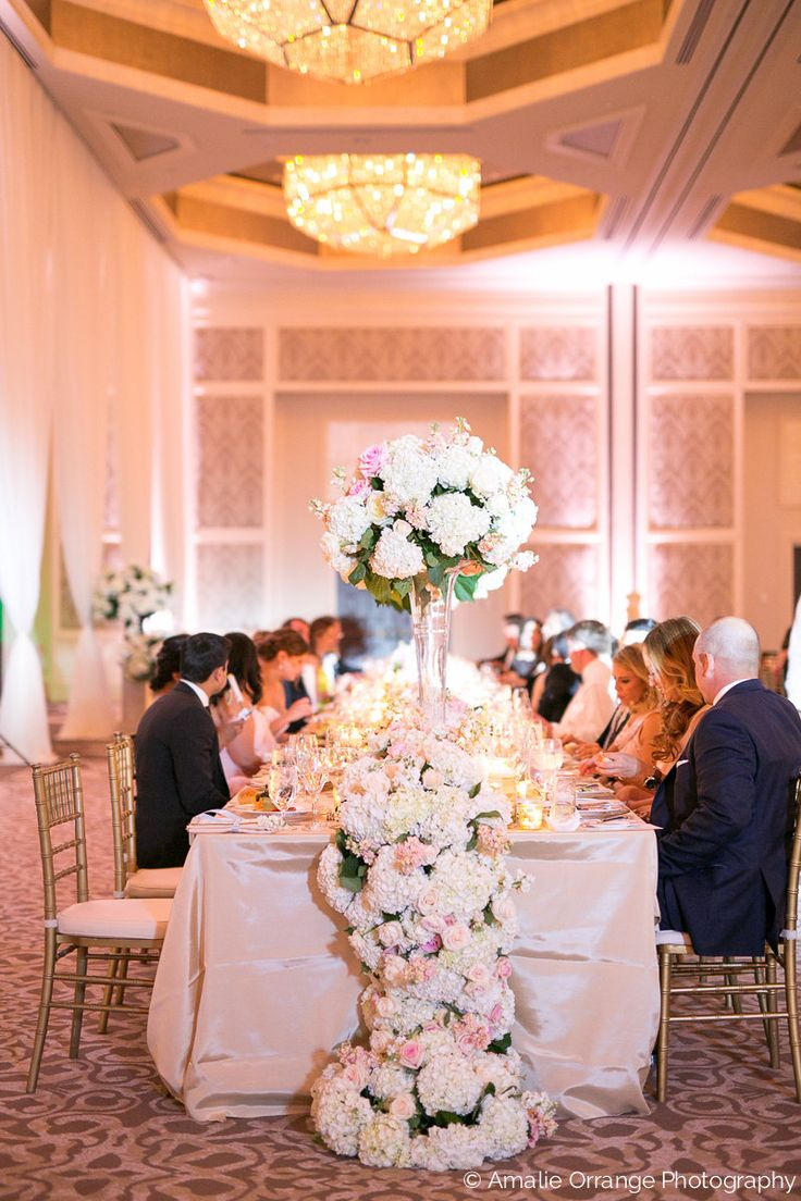 lush and grand floral table runner cascaded and pooled to the floor on both ends of the head table, featuring white hydrangea, peach, blush and ivory roses and peach stock.