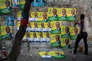 Port-au-Prince, A woman plasters electoral posters of the LAPEH party's presidential candidate, Jude Célestin, along a street in Port-au-Prince