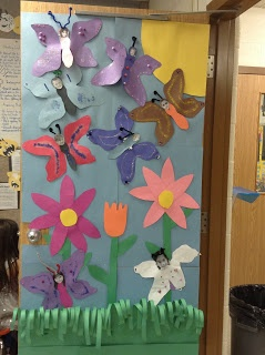 Classroom door decorated with butterflies, students faces are the head.