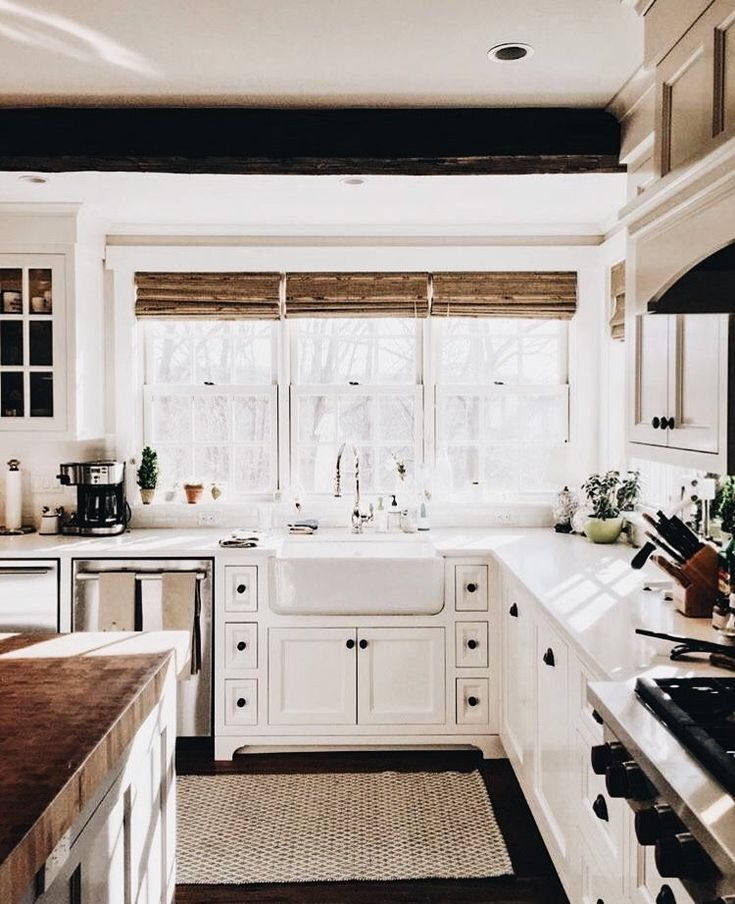 Light, airy white kitchen with black cast iron accents, stainless silver appliances, farmhouse sink, dark floor, butcher block, natural reed curtains.