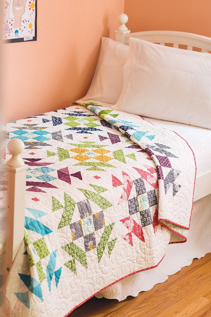 A fat quarter friendly, full-size quilt pattern, Old & New by Kimberly Jolly, uses bright triangle-squares to make a statement. It's rated easy so everyone can make it! Gather your fat quarters and set to work on this one. We walk you through making quick triangle-squares in our free video.