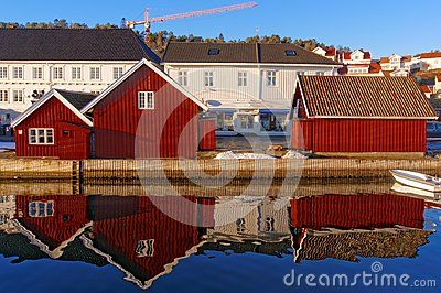Red old buildings on the mirror image in the water. In the background, the old white wooden buildings harbor. The street lies the snow and ice. The distinctive buildings. Kragero, Telemark municipality. Region of southeastern Norway. Skagerrak coast.