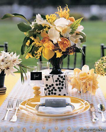 A black-and-white springtime arrangement of lemons, black elderberries, cattleya orchids, tuberous begonias, gloriosa lilies, and 'golden celebration' roses