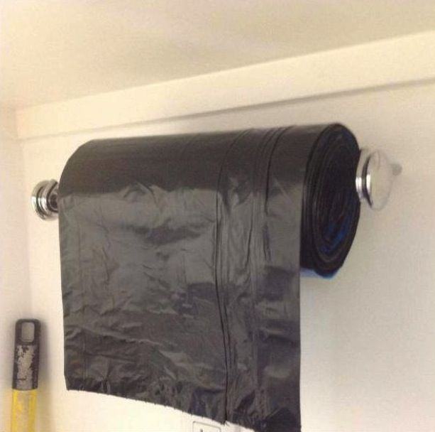paper towel holder for garbage bags, hung in the broom closet