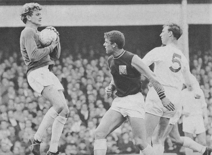 21st November 1964. Gary Sprake proving to be a safe pair of hands as West Ham United centre forward Geoff Hurst attempts to blindside Jack Charlton, at Upton Park.