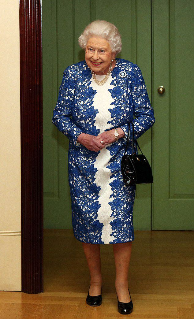 Queen Elizabeth II looks glamorous in a fitted white and blue lace dress as she throws a party for civil servants at Buckingham Palace