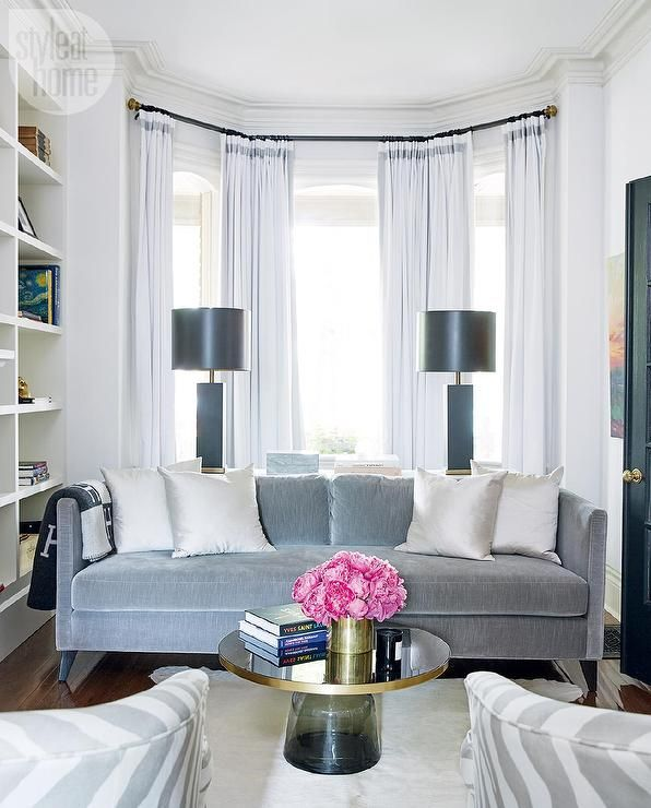 A living room bay window dressed in white curtains with a gray trim is positioned behind a gray velvet sofa topped with metallic silver accent pillows and an Hermes throw while behind the sofa a sofa table holds two gold and black lamps.
