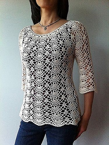 This semi-fitted top is worked from the neck down with gentle shaping below the waist for a figure skimming, flattering fit. Brimming with delicate lacy shells, this feminine piece is equally beautiful as a cropped top or tunic, with the sleeves three-quarter, slightly flared or short – the choice is yours.