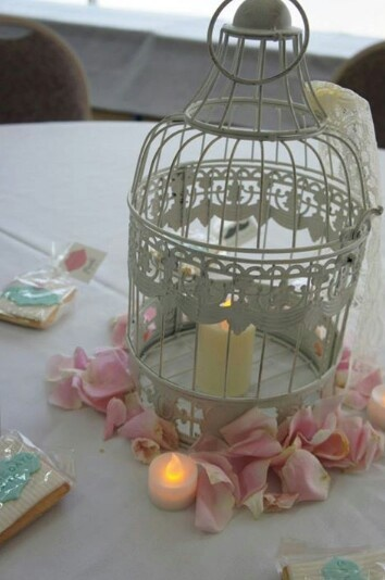 Bird cage with lace, candles and rose petals centrepiece