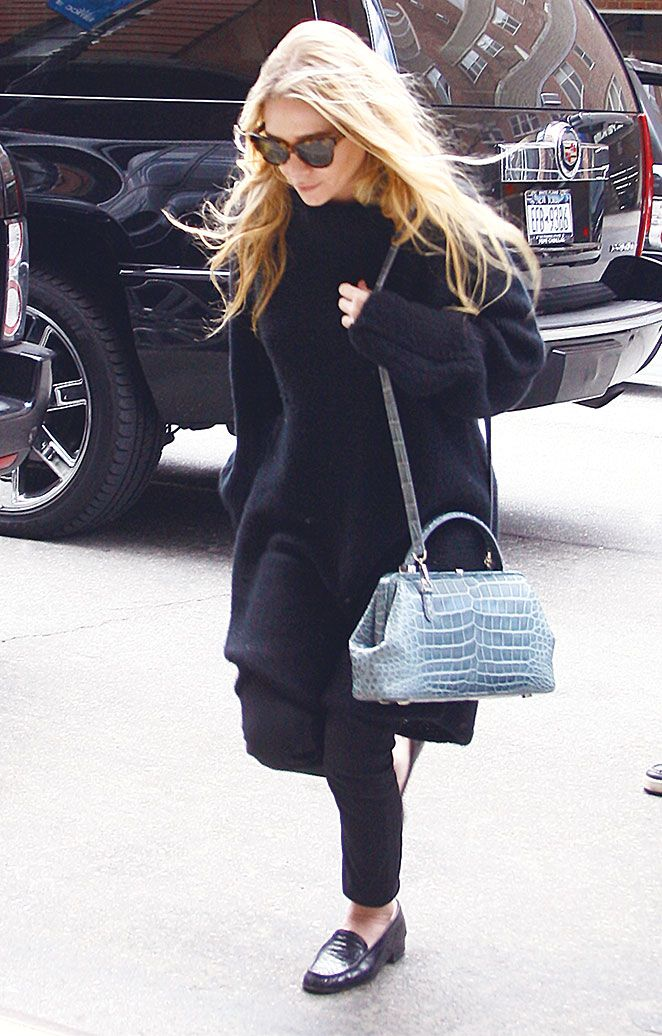 Mary-Kate #Olsen hit the streets in NYC bundled up in a thick black cashmere-sweater, black tailored trousers, #LindaFarrow for '#TheRow' cat-eye sunglasses and The Row pale blue crocodile handbag. Click to shop.