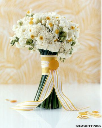 In this asymmetrical bouquet, barely yellow double narcissus mingle among classic white narcissus with yellow cups and tubular freesias that have golden throats. Wide and narrow-striped grosgrain ribbons with a pinned-on vintage button tie the tailored mix.