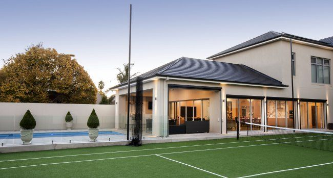 The rear of the home features all the entertaining area - a full tennis court, pool and outdoor kitchen...
