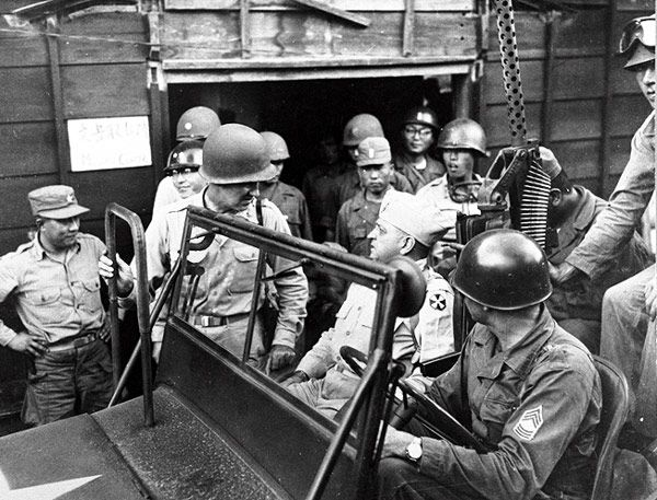 Korean Military Advisory Group chief, confers with Gen. Walton Walker (seated in jeep) during battle of the Pusan Perimeter on August 18, 1950