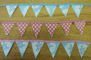 Mini bunting approx 1mt long. Made from paper and ribbon or string.  Perfect for decorating cakes or cards etc.  Handmade at Oople Eumundi
