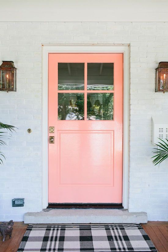 An adorable front door painted pink adds a feminine and cute touch to the home.