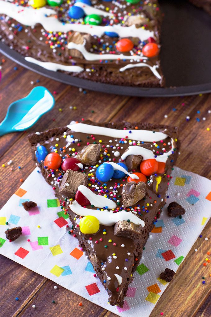 Brownie Dessert Pizza~A fudgy brownie dessert pizza topped with Nutella, M&M's, mini candy bars, SPRINKLES and drizzled with marshmallow creme. It's a dessert that will put a smile on everyone's face!