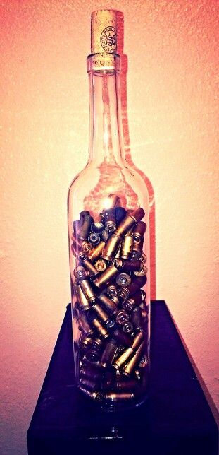 Took a clear empty wine bottle and put gun shell casings in it from a trip me and my husband took to the gun range. Great conversation and display item.