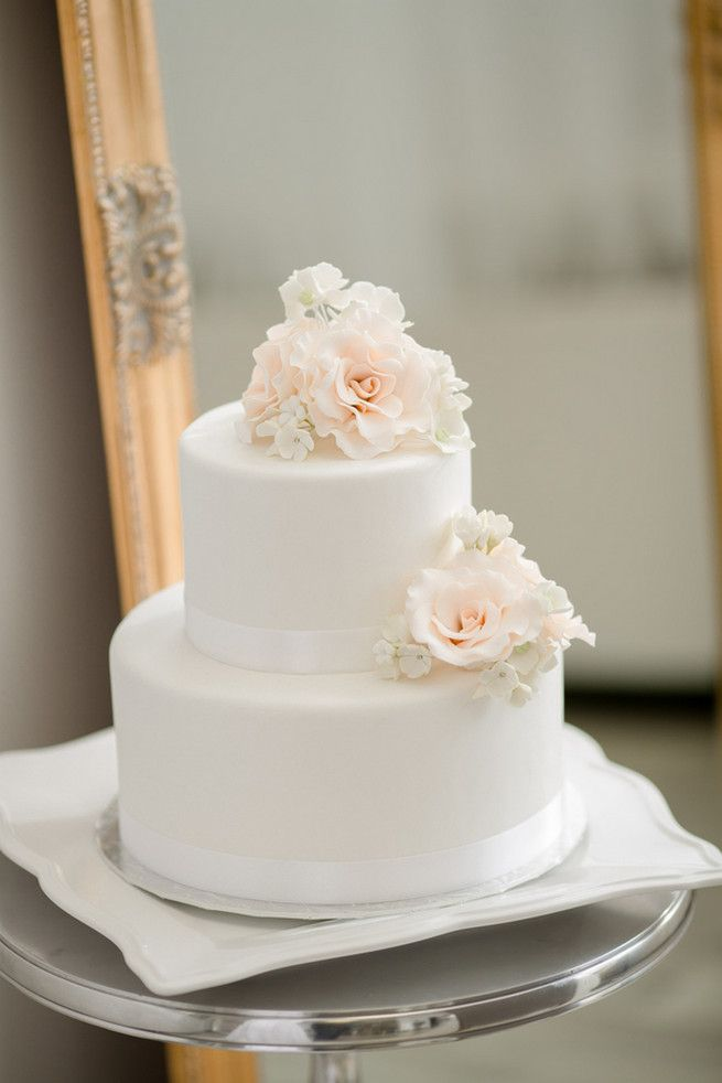 25 Amazing All White Wedding Cakes ♥ Soft peach flowers take this two tier white wedding cake from understated to unbelievable.  { Cake:  The Art of Cake | Photography: ENV Photography }